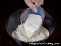 Pour warm milk mixed with sugar and dry yeast to bowl with flour